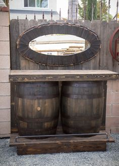 Bar is made from wine or whiskey barrels. Barrels are cut in half and sits on a base for added height. Styled with metal bar for an industrial finish. Back has shelf for storage of bottles and accessories.