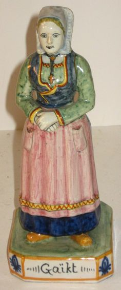 """HR Quimper Figure of a Bretonne with the name """"Gaikt"""" painted on the base. Bretonne has folded hands and is wearing a traditional coif and a cross on a chain. 8 1/2""""H. Marked HR Quimper on back of base. Literature: see """"Quest for Quimper"""" pg.205. c.1910."""