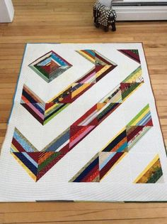 Scrappy half square triangles make a simple quilt look extra fancy. The quilting is concentric circles starting with the colored square.