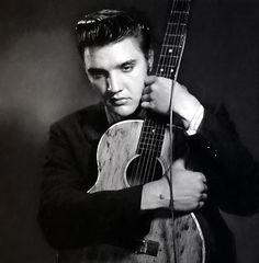 Elvis Presley bonding with his guitar...