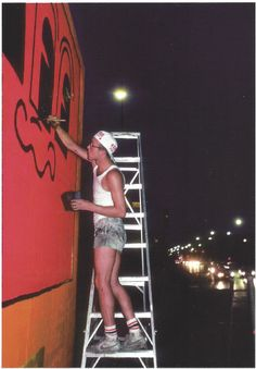 Keith Haring painting mural on Houston Street wall, Manhattan, NYC 1982 - Martha Cooper