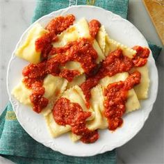 Homemade Ravioli Recipe Main Dishes with all-purpose flour, eggs, water, olive oil, sauce, crushed tomatoes, tomato purée, grated parmesan cheese, water, tomato paste, sugar, fresh basil, fresh parsley, fresh oregano, garlic cloves, salt, pepper, ricotta cheese, part-skim mozzarella cheese, grated parmesan cheese, eggs, fresh basil, fresh parsley, fresh oregano, garlic powder, salt, pepper