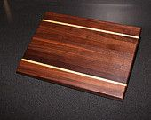 """Solid, walnut wood edge-grain cutting board with rock maple accent. Smooth flat surface for chopping, slicing, dicing, mincing, and more Smart alternative to plastic--easier on knives and won't harbor bacteria Hand wash and oil regularly for best results Measures 11-1/2"""" x 8-3/4"""" by 1""""  Website: www.simplywoodproducts.ca"""