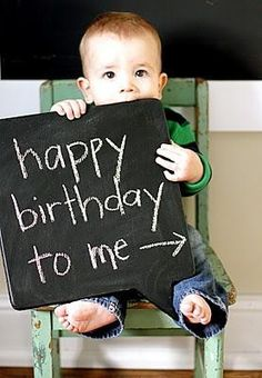 El día de su primer cumpleaños posando con una pizarra con mensaje