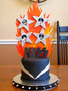 KISS Cake! - KISS Cake for some friends who are going on the KISS Kruise! Six inch round chocolate fudge cake with dark chocolate frosting, covered and decorated with fondant. 2D flame plaque and stars are made from gumpaste. Stars are brushed with silver luster dust and sparkly disco dust. Lightning is brushed with an edible silver luster dust. Band faces are cupcake picks, and band logo is a plastic cake topper. Spikes on cake board are metal spike studs that I hammered into the cake…