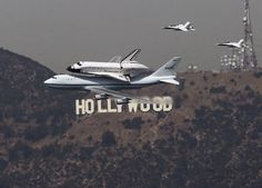 The Space Shuttle Endeavour is escorted by two F-18 jets as it passes the Hollywood sign on the back of a NASA 747 in Los Angeles.  Very cool shot.