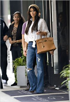 Kim Kardashian seen wearing white checkered shirt and flared jeans while visiting The Children's Museum of Manhattan in NYC