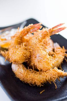 Giant prawns covered with crisp golden brown tendrils of shredded coconut with a hot and tangy orange chili dipping sauce. Perfect coconut shrimp for parties.