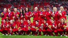 Canada's women's soccer team pose for a team photo after being presented with their bronze medal at the 2012 Summer Olympics