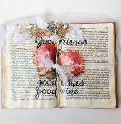 A shabbied up book that is ready to hang like a picture. In the middle are pretty pink-red florals and quote, good friends, good times, good wine. Great for the book lover