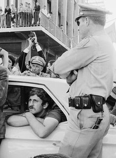 Jack Weinberg sits in a police car after his arrest during the Free Speech Movement for not showing his ID. Protesters surrounded the car and prevented it from moving for 32 hours, until the charges were dropped (October 1, 1964).