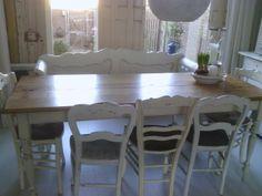 een smalle franse eettafel met antiek bankje, en hele oude stoeltjes. zo'n gezellige eethoek!