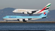 Korean Air Boeing 747-8i taxiing at San Francisco as an Emirates Airbus A380-861 lands on the adjacent runway