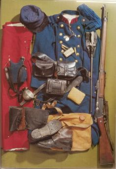 French infantryman kit, Aug. 1914. From left to right: trousers m. 1867/93, kepi m. 1884 with cover, greatcoat m. 1877, ID plaques m. 1881, neck tie, 1-liter canteen m. 1877, cup m. 1852, suspension braces m. 1892 with cartridge pouches mo. 1888, frog m. 1888, Lebel m. 1886/93, gaiters m. 1913, boots m. 1912/16 (not worn in 1914), haversack m. 1892 .