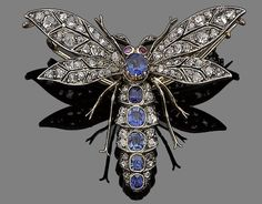 A late 19th century sapphire, ruby and diamond dragonfly brooch, circa 1890  The abdomen centrally-set with cushion-shaped sapphires, between duos of rose-cut diamonds, to similarly-cut diamond wings, the head highlighted with two circular cabochon ruby eyes, mounted in silver and gold, removable brooch fitting,