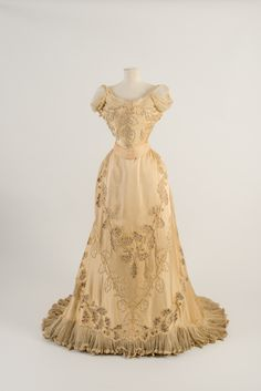 Evening dress, Worth, 1903. Pale yellow satin with oak leaf embroidery in white silk cord and cream chenille, net inserts. Worn by Mary Curzon. Fashion Museum Bath.