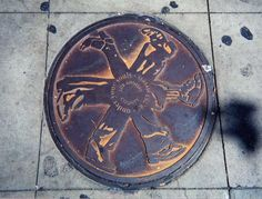 "Manhole cover, Grand Central Market, Los Angeles, California. Text reads ""under your souls - 38,753 streets."" Photo date 2001."