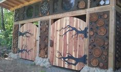 Amazingly beautiful and detailed cordwood shed. Click through for a triquetra heart knot carved by the door.