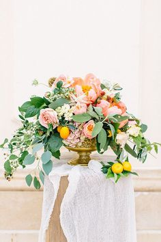 Floral designer Evelyn Kühr filled an ornately carved gold compote to overflowing with a brightly lush mix of garden roses, parrot tulips, peonies, hydrangeas, astilbes, unripe blackberries, lemon branches, olive branches, and scabiosa pods. | Photo by Tony Gigov
