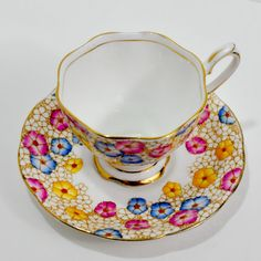 Beautiful hand painted Royal Albert Crown China teacup and saucer from England in perfect condition. This set is hand painted in pink, yellow, and blue trim and decorated with gold trim. This set is signed and numbered, has a delicate design and has a back stamp that dates it to