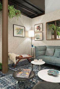 Ambiente decorado para a mostra Modernos e Eternos com sofá, poltrona de madeira, quadros, obra de arte, fotografias, tapete cinza, mesa de centro, plantas, espelho e adornos.