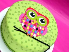 Owl cake, decorated in fondant. Those colours are amazing. The details and work involved here is deceptive. If you are going to try to replicate this, have a bit of time to spare.  There will be a little bit of prep work, but wow it will be worth it.