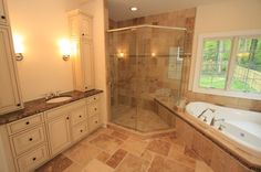 Lenox Model. Master bathroom with stone floor, deep soaking tub, and a glass shower.