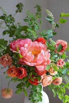 Stunning peony and ranunculus floral arrangement in pink, coral, orange, and peach colors.