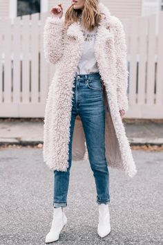 Jess Ann Kirby dresses up a tee shirt and jeans with white ankle booties and a faux fur coat