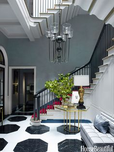 Vivid red carpet on the stairs and a black-and-white marble floor with boldly scaled octagons establish the entry's dynamic mood.