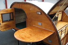 Closeup view of teardrop camper with side table and rear galley open.
