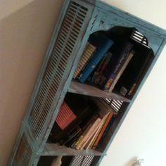 Spray painted, then sanded with sandpaper for a distressed bookshelf.