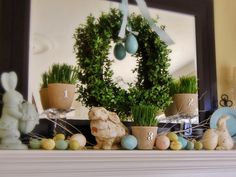 Decorating a fireplace mantel can be challenging, but if executed properly, can make for a beautiful focal point in a room.  Let the designers of Sister Bay Trading Co. assist you in creating the perfect mantel for any occasion.  A tranquil color scheme pulls this Easter mantel together. The boxwood wreath & blue plastic egg are hung to a large mirror. Vintage bunnies in light blue & cream add to the color scheme & potted grass complete the simple spring look.