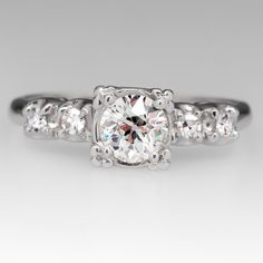 This vintage ring features a lovely centered round .61 carat Old European cut diamond grading H in color and I1 in clarity. The shank of the ring is crafted of platinum with the diamond set into an illusion style head. The ring is accented with two round single cut diamonds on each shoulder. We can resize to fit prior to shipping.