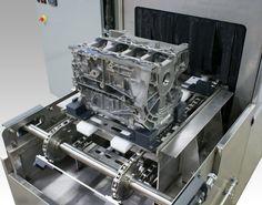Engine block fixture on conveyor washer.