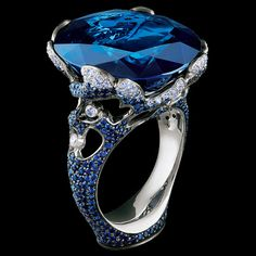 1 oval sapphire 25,47-25,50 ct  92 diamonds 0,33-0,36 ct  362 sapphires 2,11-2,14 ct  18K white gold 9,4-10,4 g
