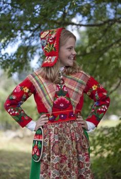 Sweden. This girl wears a mix of embroidery, plaid and floral fabric.