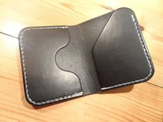 The Wheelright a compact and convenient small wallet to hold everything you need when you want to travel light, it has 2 dedicated card slots (1 internal and 1 external for rapid access) which will hold 3 cards each and a folded note compartment. Made from dyed black veg tan shoulder leather. All work done by hand in a time honored tradition, cutting, awling, stitching, sanding and burnishing. A wallet whose looks will only improve with age and use. Wallet comprises, 2 x dedicated card…