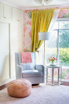 Nursery with large windows, floral wallpaper, and a small side table