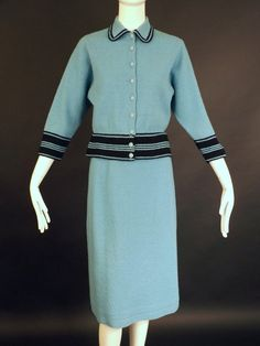 Late 1940s sweater dress consisting of a cardigan and a slender skirt. The cardigan is trimmed in navy with a spread collar and button closures down the front. Dart fitted at the bust. 3/4 Set in slee