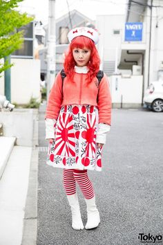 This red-haired girl wearing a mostly red outfit is Mai. Mai's kanji print dress is from Nincompoop Capacity, which she paired with a crop sweatshirt. She is wearing a randoseru (Japanese school bag) and wedge tabi boots from Sou Sou with knee high striped socks. Her hat features a cross and bows. She likes shopping at Dog Harajuku, and she's an anisong fan.