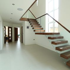 my favourite staircase, glass to make it look floating, i like the wooden stair treads to link in with the wooden beams, and the wooden banisters on top of the glass to make them safe for family members