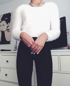 fuzzy white sweater, black high-waisted jeans, light blue nails.