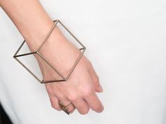 Printed using stainless steel powder, this 3D printed bracelet comes out looking like a perfect silver cube.