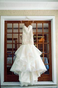 Hayley Paige Yoko gown hanging in front of french doors  BHLDN hanger