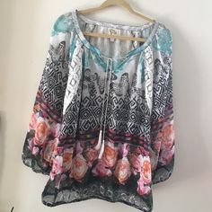Fig and Flowers Tunic Top Print in a variety of colors with flows and butterflies. Sheer material with a tie at the collar. Sleeves are long roomy. Excellent condition, I never wore it. Fig and Flowers Tops Tunics
