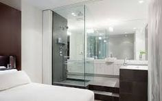 bathroom open to bedroom with dark cabinets and glass shower