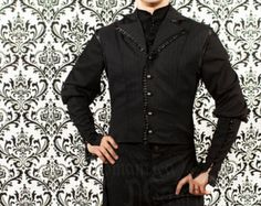 An elegant black cotton shirt with buttons and lace detail. The shirt features a mandarin collar, a shaped hem, and lace trim at the wrists as well as flanking the front row of buttons (lace may differ from photo). The sleeves are loose around the upper arm and fitted to the forearm, where they close with black buttons. This item is machine washable and dryer safe.  The photos show the sleeves fastened with button loops, however please be aware that your shirt will have buttonholes instead…