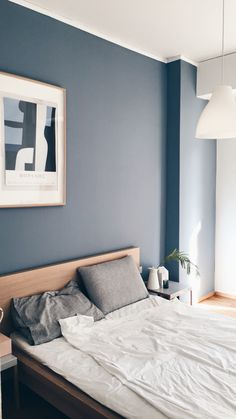 Minimalist bedroom with blue grey wall and moralis painting hanging on the wall.