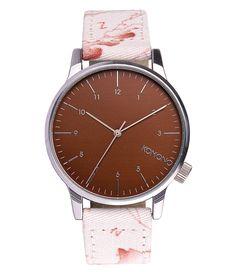 Dit Komono Winston Print horloge heeft een donkerbruine klok, en een licht roze band.